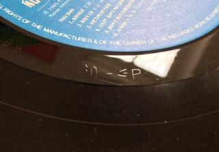 Plade fra Grammoplast med GP indridset